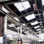 Светлый излучатель от Schwank под потолком промышленного здания.